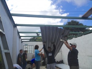 Avenue Church's men's team hoisting up the new sheets of metal roofing.