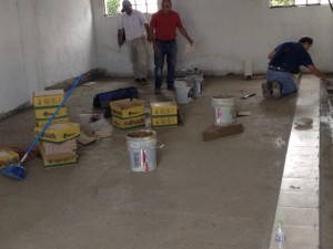 Laying tile on the newly poured floors.