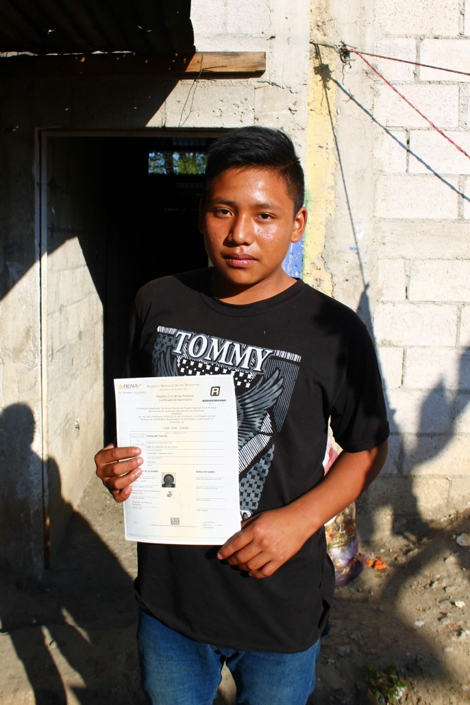 Juanes proudly displaying his government registration which will allow him to enroll in school, apply for jobs, and one day get married.
